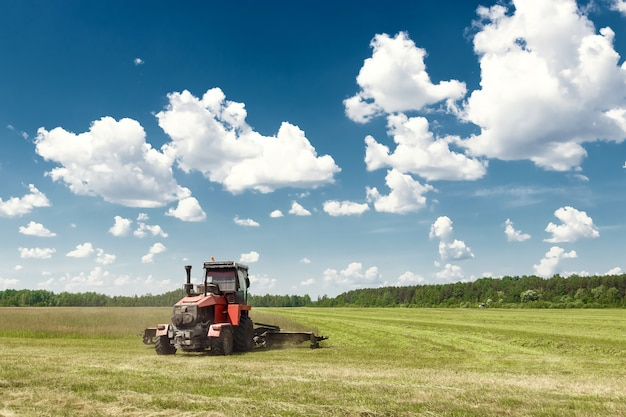 Agricultural machinery, harvester mowing grass in a field against a blue sky Premium Photo