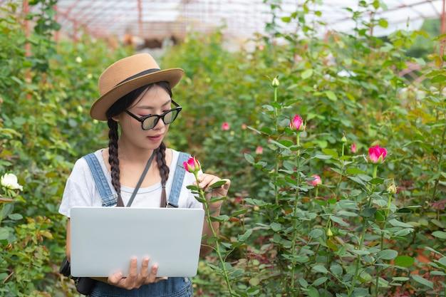 バラ園でタブレットを保持している農業の女性。 無料写真