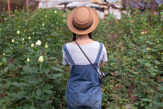 Agricultural woman holding a tablet in the rose garden. Free Photo