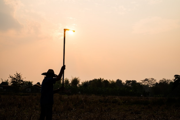 Agriculture farmer life concept: black silhouette of a worker or gardener holding spade is digging soil at sunset light Premium Photo