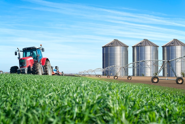Agriculture and food production concept with tractor machine silos and irrigation system Free Photo