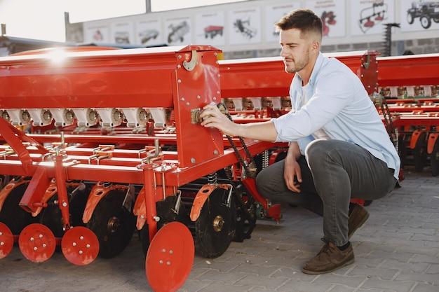 Agronomo che sceglie una nuova fioriera. uomo al suolo all'aperto del negozio. macchinari agricoli. Foto Gratuite