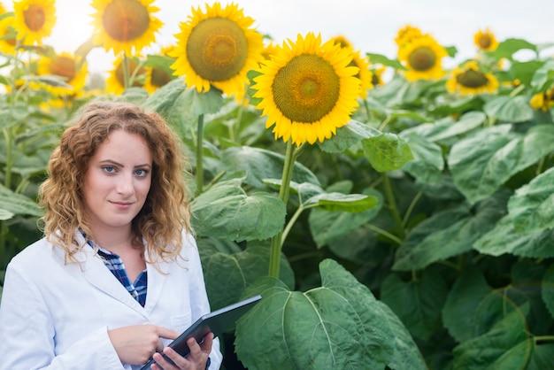 Scienziato agronomo in abito bianco che tiene tavoletta digitale nel campo Foto Gratuite
