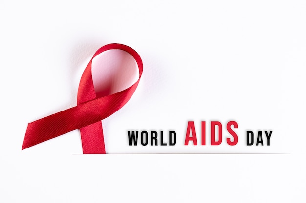 Aids awareness red ribbon on white paper with text. world aids day concept. Premium Photo