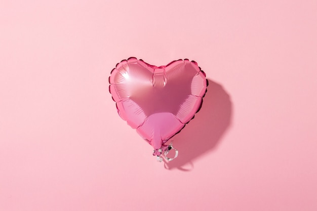 Air balloon heart shape on a pink background. natural light. banner.  love, wedding, photo zone. flat lay, top view Premium Photo