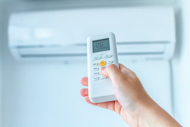 Air conditioner temperature adjustment with remote controller in room at home. Premium Photo