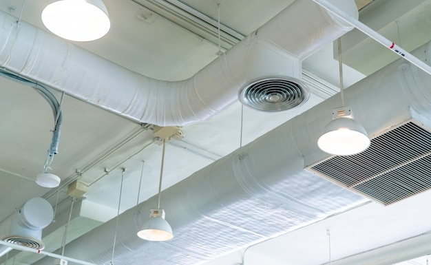 Air duct, air conditioner pipe and fire sprinkler system on white ceiling wall. ceiling lamp light with opened light. interior architecture concept. Premium Photo