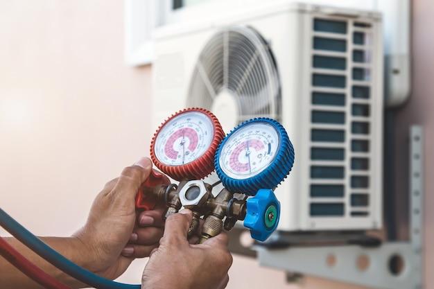 Ремонтник-механик использует измерительное оборудование для заправки домашнего кондиционера. Premium Фотографии