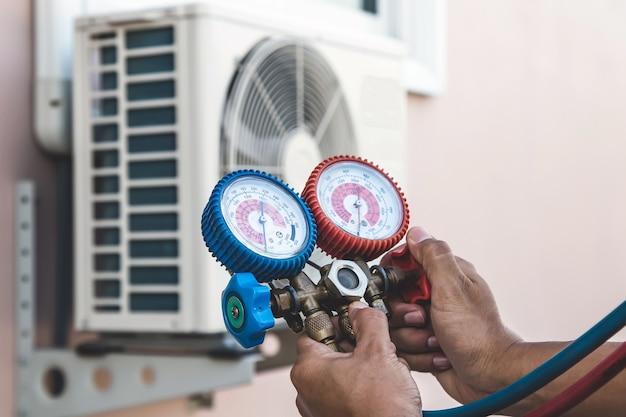 Слесарь по ремонту воздуха использует оборудование для измерения давления для наполнения домашнего кондиционера. Premium Фотографии