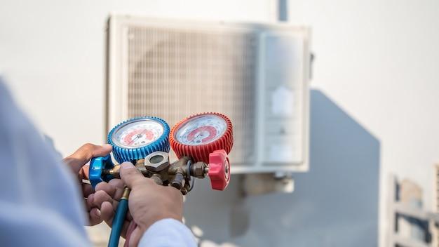 Ремонтник воздуха, использующий манометр для заполнения промышленных заводских кондиционеров Premium Фотографии