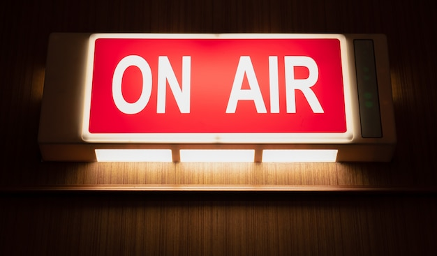 On air sign icon glowing on the wooden wall of sound recording studios Premium Photo