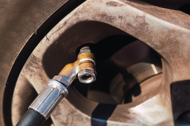 Air valve of a car tire next to the pressure gauge to swell it. Premium Photo