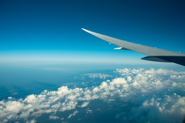 Aircraft flying above the clound and blue sky. nice view from the airplane window. Premium Photo