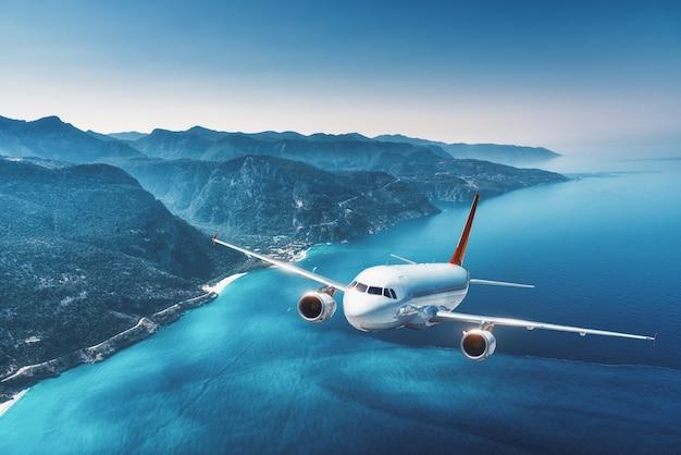 Летом на восходе солнца самолет летит над островами и морем. пейзаж с белым пассажирским самолетом Premium Фотографии