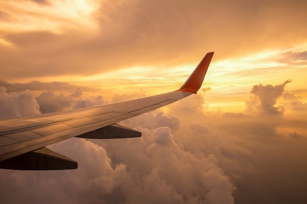 Aircraft wing on the clouds of sunset Premium Photo