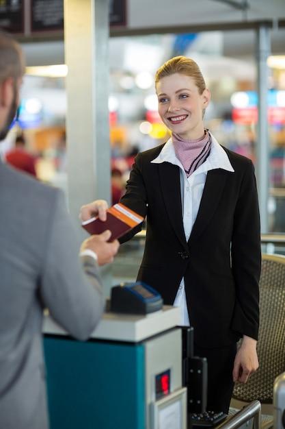 Addetto al check-in della compagnia aerea che consegna il passaporto al pendolare Foto Gratuite
