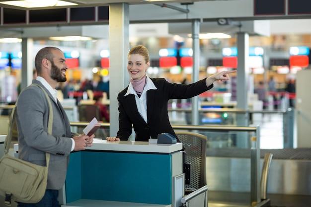 Addetto al check-in della compagnia aerea che mostra la direzione del pendolare al banco del check-in Foto Gratuite