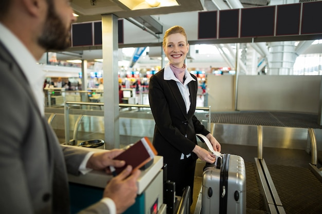 Airline check-in attendant sticking tag to the luggage of commuter Free Photo