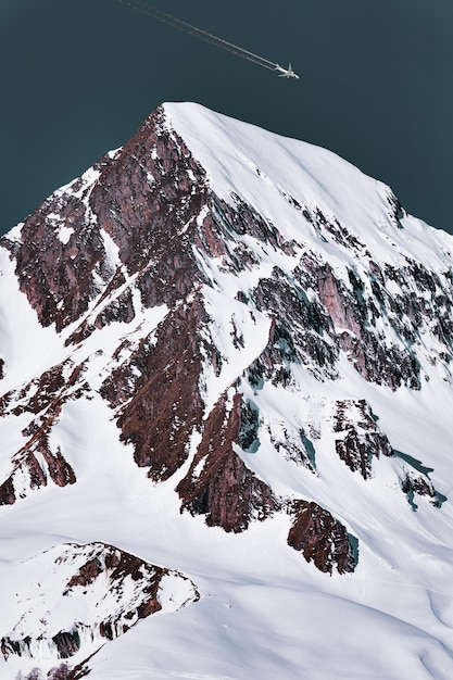 雪に覆われた山の頂上を通過する飛行機雲と旅客機 無料写真