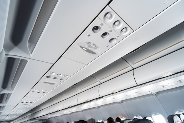 Airplane air conditioning control panel over seats. stuffy air in aircraft cabin with people. new low-cost airline. Premium Photo
