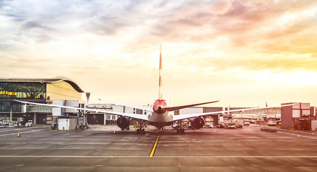 Airplane at airport with multicolored sunset filter Premium Photo