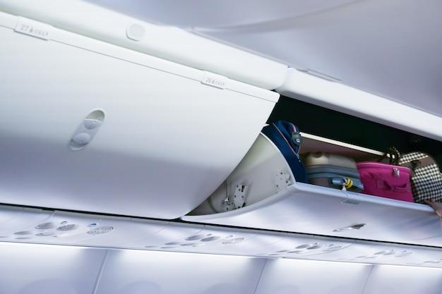 荷物コンパートメントを備えた飛行機のキャビン、機内での出発準備の荷物 Premium写真