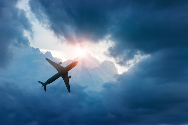 Airplane in the dark blue sky and cloud Premium Photo