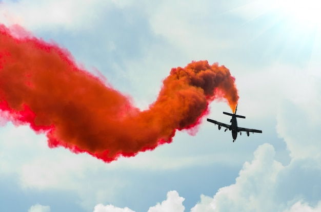 Airplane fly in zigzags with a red trail smoke in the sky. Premium Photo