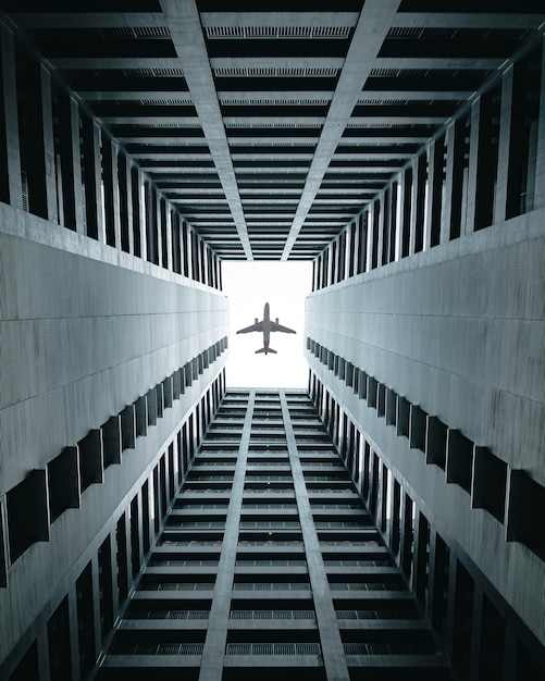 Airplane flying over the buildings. Free Photo