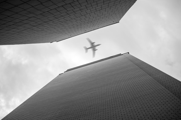 Airplane flying over skyscrapers. bottom-up view. Premium Photo