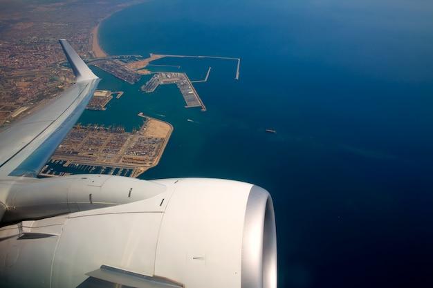 Airplane flying over valencia mediterranean port spain Premium Photo