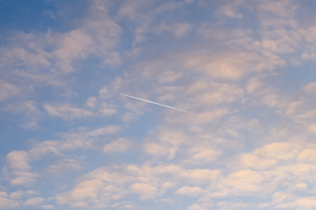 夕焼けの青い曇り空の飛行機。 Premium写真