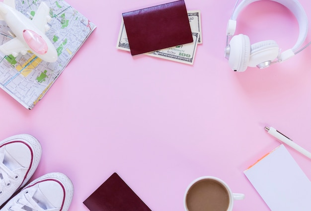 Airplane; map; passport; banknotes; footwear; earphone; tea; paper and pen on pink background Free Photo