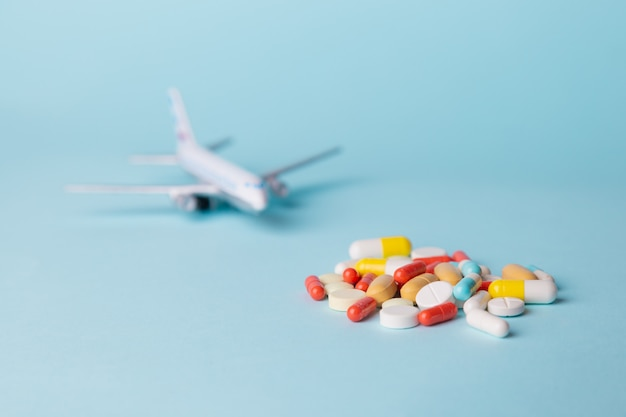 Airplane model with multi-colored pills from motion sickness scattered Premium Photo