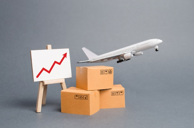 Airplane plane takes off behind stack of cardboard boxes and stand with red up arrow Premium Photo