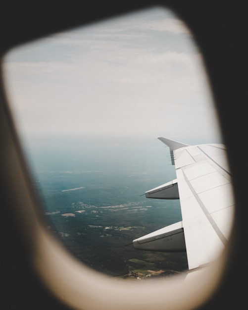 Airplane's window with the view of the green fields above and the right-wing Free Photo