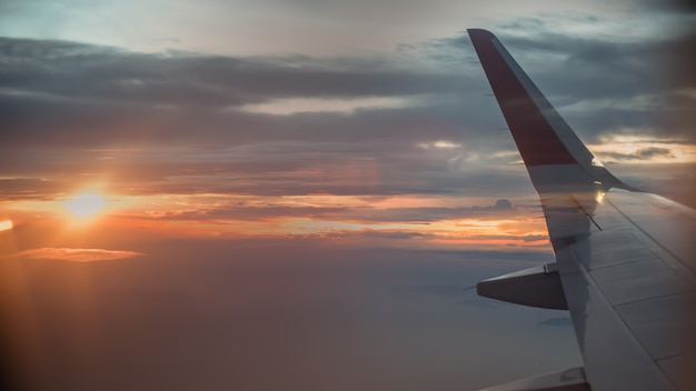 Airplane Window View With Wing At Sunrise Premium Photo