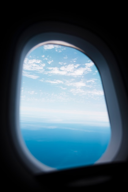 Airplane window with sky and sea lanscape Free Photo