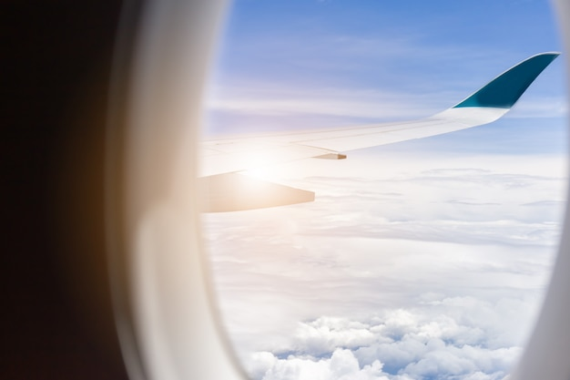 Airplane wing view out of the window the cloudy sky background Premium Photo