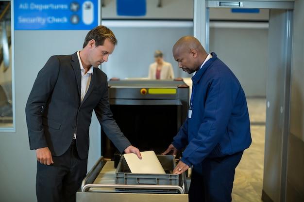 Addetto alla sicurezza aeroportuale che controlla il pacchetto del passeggero Foto Gratuite