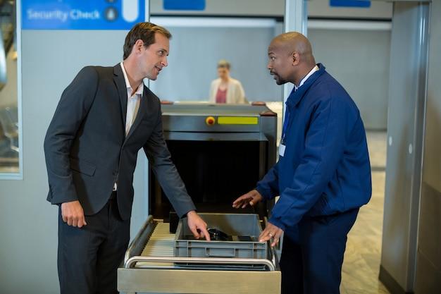 Funzionario di sicurezza aeroportuale che interagisce con il pendolare durante il controllo di un pacco Foto Gratuite
