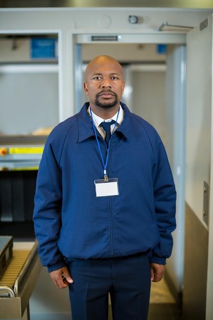 Funzionario di sicurezza aeroportuale in piedi nel terminal dell'aeroporto Foto Gratuite
