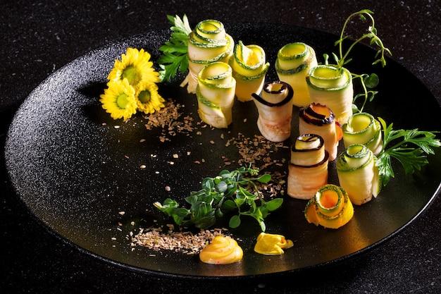 Аджвар цукини роллы из гриля подается на черной тарелке на темном фоне. меню и концепция дизайна. Premium Фотографии