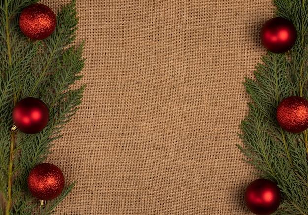 両側に赤いクリスマスボールと緑のakの木の枝。 無料写真