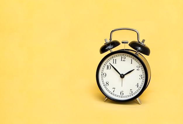Alarm clock analog classic vintage black on pale yellow background. Premium Photo