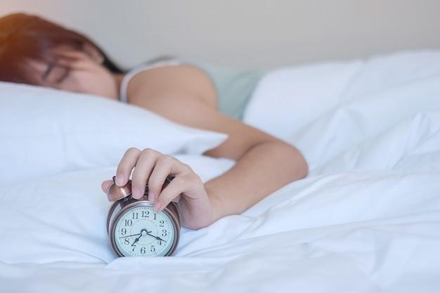目覚まし時計とアジアの女性の手が寝ている間にベッドで時間を停止し、若い大人の女性が朝遅く目を覚ます。新鮮なリラックス、眠い、素敵な一日のコンセプト Premium写真
