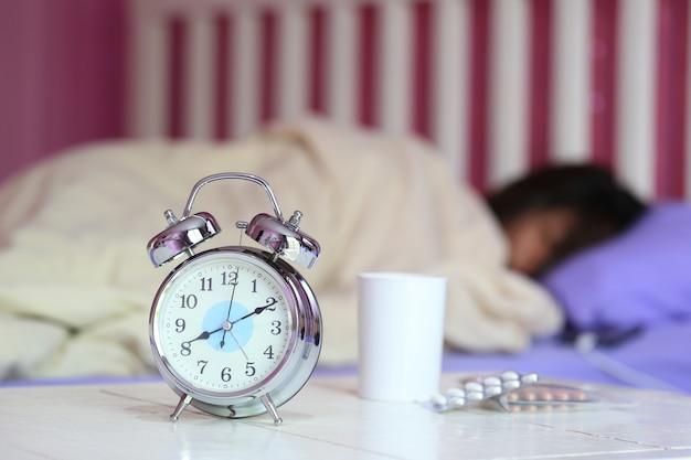 目覚まし時計と水のガラス、寝室で寝ている女性と薬 Premium写真