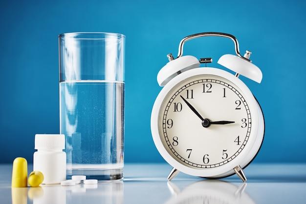 目覚まし時計とピルと水のガラス Premium写真