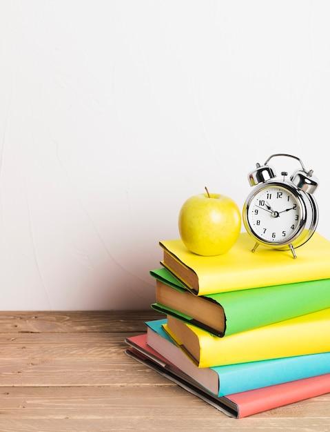 Будильник и желтое яблоко на стопке учебников Premium Фотографии
