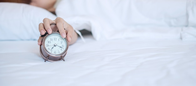 Alarm clock and asian woman hand stop time in bed while sleeping, young adult female wake up late in the morning. fresh relax, sleepy and have a nice day concepts Premium Photo